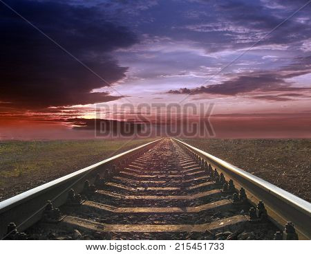 gloomy landscape with rails going away into the far sunset. Evening landscape with rails
