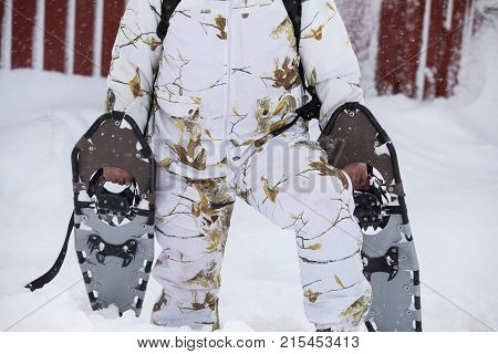 Winter snowshoeing. Man wearing winter camouflage clothes holding snowshoes outside his red cabin in the snow, when snowing. No head visible in the image