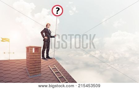 Young businessman wearing helmet with roadsign on roof edge. Mixed media