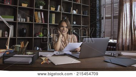 Work brings positive emotions. Young smiling business woman sitting in office chair behind desk with paper and mug of coffee tablet and laptop and holding in hand documents. Business work in studio