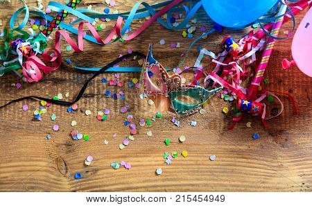 Carnival Party. Mask, Confetti And Serpentines On Wooden Background, Top Niew