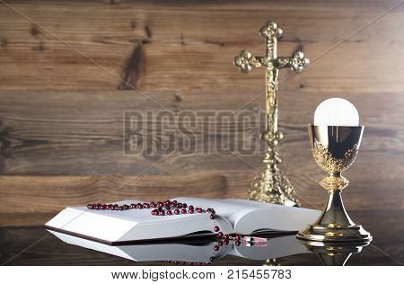 Holy communion concept. Holy Bible, rosary and golden chalice on wooden background.
