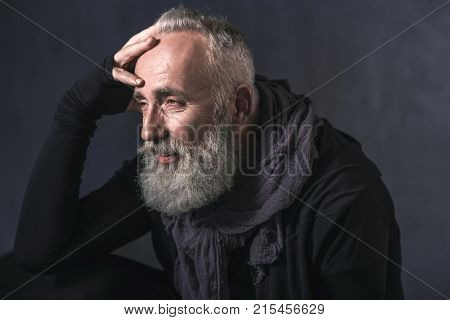 Side view smiling bearded senior locating in apartment. Reverie concept