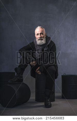 Full length portrait of serene bearded old man locating on iron casks in apartment. Reverie concept
