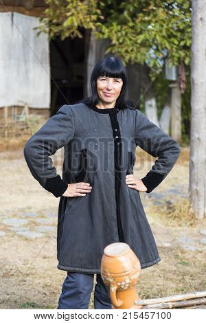 Smiling woman with black hair in ancient national clothes stands near the fence against the backdrop of rural farmstead. Ukrainian village. Ukraine