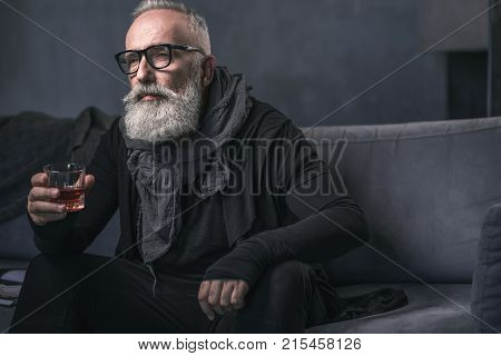Portrait of serene unshaven grandfather drinking alcohol while sitting on cozy sofa in apartment. Rest concept
