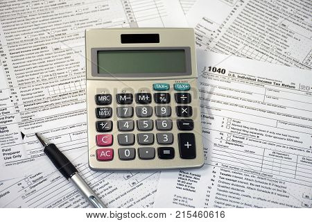ball point pen and calculator on federal 1040 income tax form
