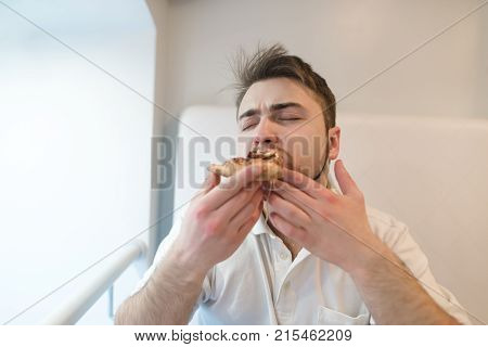 The man closed his eyes from swaddling while eating a tasty pizza. A man eats with his hands a piece of appetizing pizza.