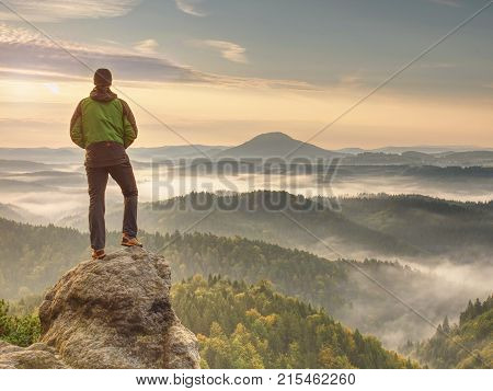 Hiker Is Standing On Sandstone Peak In Rocky Park And Watching Over Misty And Foggy Morning Valle
