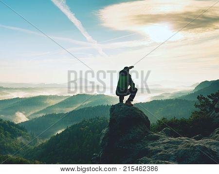 Hiker Man Take A Rest On Mountain Peak. Man Sit On Sharp Summit And Enjoy Spectacular View.