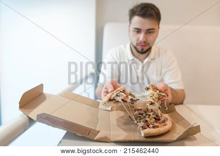 A man sits at the table near the box and holds in his hands a few pieces of pizza. The man eats a hot pizza