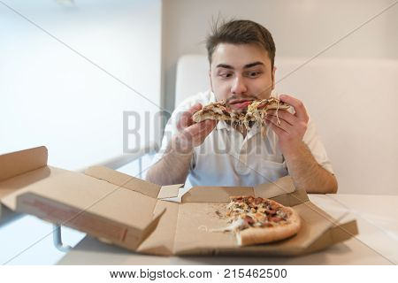 Funny man with a beard eating pizza from a cardboard box. A man holds pieces of pizza in his hands and is going to eat them.