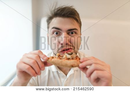 Portrait of a funny man with a piece of pizza in his hands. The man eats a pizza and looks at the camera. Fast food lunch.
