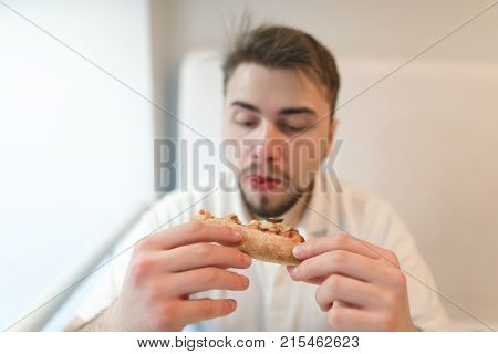 A hungry man looks closely at a piece of pizza in his hand and is about to eat it.