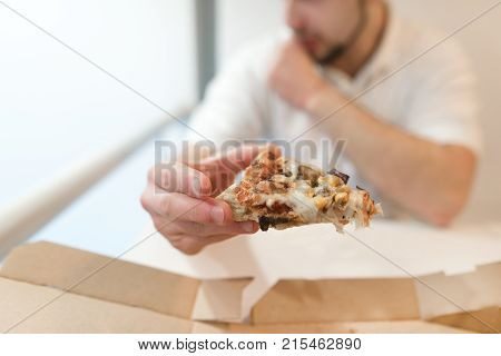 A man holds a piece of pizza in his hands. The man eats a pizza. Focus on a piece of pizza