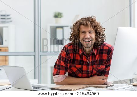 Smiling businessman in casualwear sitting by his workplace in office