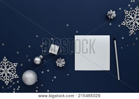 Silver blank Christmas card and a pencil with silvery New Year decorations gift snowflakes & sequins on dark blue background. Top view