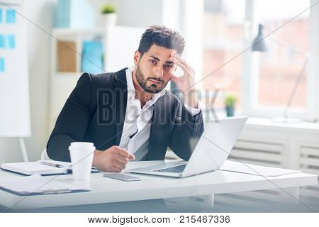 Pensive businessman concentrated on work organization or solving financial problems sitting in front of laptop in office