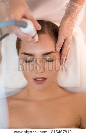 Top view close up of relaxed girl enjoying facial massage while beautician is moving laser over her forehead. Skincare concept