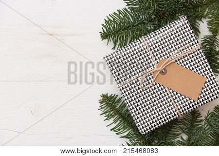 Christmas gift box with tag. New Year present in black and white box with fir branches at white wooden table. Flat lay with copy space. Celebration holiday season and winter concept
