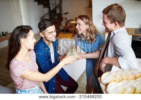 Two young couples clinking by their drinks at home party on friday night