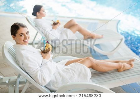 Happy young woman with tropical drink looking at camera at spa resort with her relaxing friend on background