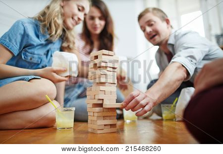 Group of friends bulding tower from wooden bricks on the floor