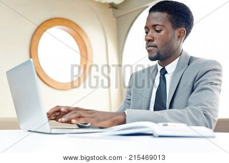 African-american specialist typing on laptop inside steamship and organizing work