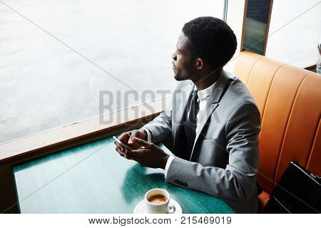 Young man in elegant suit sitting by table in steamship while traveling