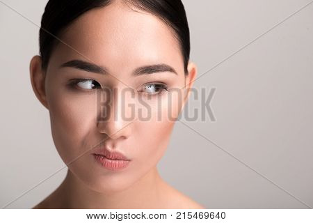 Close-up portrait of dissatisfied young asian woman is drawing faces in front of camera. She is standing and looking aside with discontent. Isolated background with copy space in the right side