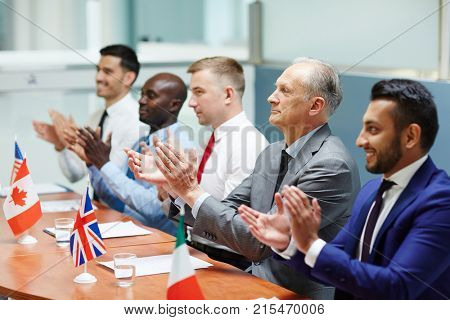 Satisfied leaders of several countries clapping their hands after report of colleague