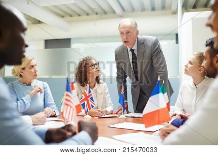 Mature politician in suit explaining strategy of eu development to young colleagues