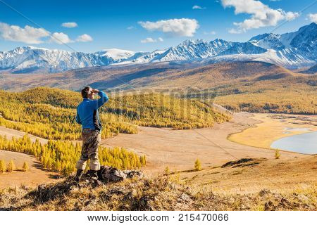 A Man looking at the Mountains and a Lake below from Viewpoint. Altai. Siberia
