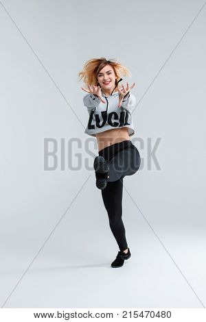 Young girl, dancer, in black leggings and a gray sweater, shows dance elements, in studio standing on one leg, holding hands forward, isolated on white background.