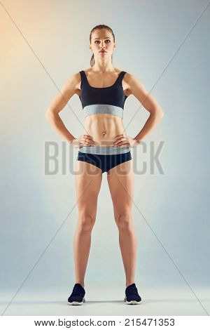 Sport is life. Full length shot of an athletic young lady wearing a navy blue sportswear standing with her arms on the hips and looking ahead.