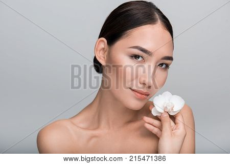 Sense of beauty. Positive elegant young asian naked girl is looking at camera wistfully while holding white flower. Tenderness and softness skin concept. Isolated background