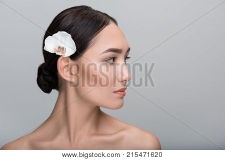 Natural beauty style. Close-up profile of face of young naked charming asian woman with white orchid is in her hair. She is looking aside thoughtfully. Isolated background and copy space in right side
