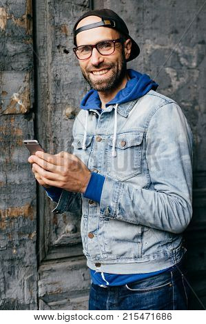 Fashionable Young Bearded Man In Cap, Denim Shirt And Eyeglasses Holding Smartphone In His Hands Mak