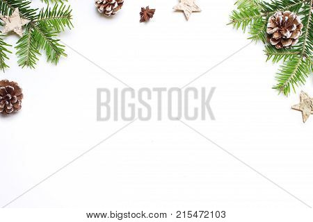 Christmas festive styled stock image. Floral frame composition with pine cones, fir tree branches, wooden and anise stars on white wooden background, flat lay, top view with empty copy space.