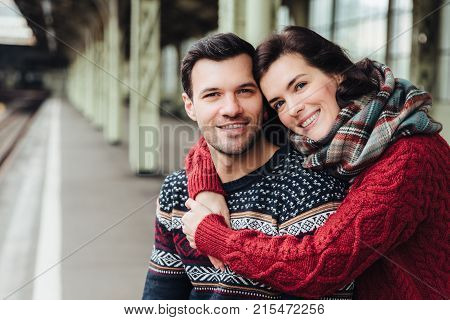 Portrait Of Happy Young Female Embraces Her Husband, Smiles Happily, Going To Travel Together, Wait