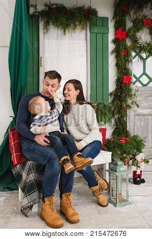 Happy Parents With Little Son. Child Boy In Sweater Sitting On Bench At Light House With Decorated I
