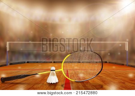 Low angle view of badminton arena with sports fans in the stands and copy space. Focus on foreground racket and shuttlecock with deliberate shallow depth of field on background. Camera flashes and lens flare for special effect.