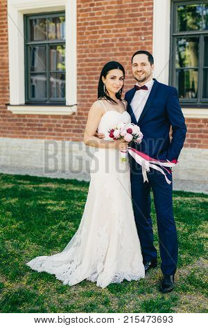 Vertical Portrait Of Happy Bride And Bridegroom Stand Next To Each Other, Wait For Guests, Celebrate