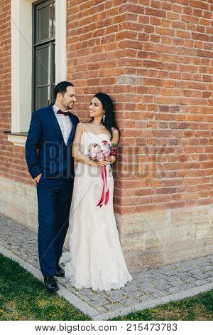Handsome Male Bridegroom Looks With Great Love At His Bride. Happy Newlyweds Stand Near Brick Wall O