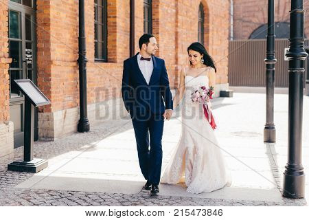 Horizontal Portrait Of Affectionate Lovely Married Couple, Keeps Hands Together, Walk Outdoor, Look