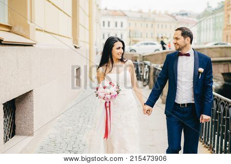 Attractive Female With Dark Hair, Wears White Dress, Holds Bouquet, Keeps Bridegroom`s Hand, Look At