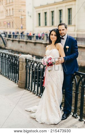 Handsome Bearded Bridegroom Embraces His Bride In White Dress With Bouquet Stand Together At Bridge,
