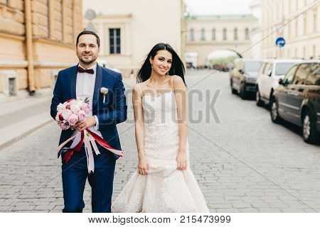 Bridegroom And Bride Have Walk Together, Pose At Camera, Have Pleased Expressions, Celebrate Their W