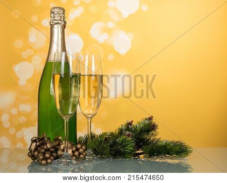 Bottle of champagne two glasses decorated pine branches on bright yellow background
