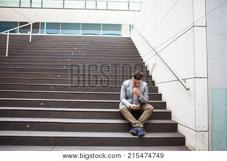 Busy male manager checking email on gadget outdoors. Thoughtful mixed race businessman solving work issue using gadget while sitting on step. Business in city concept